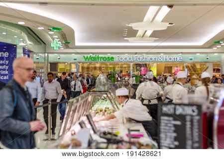 London UK - May 15 2017 - Waitrose Food Fashion & Home a chain of British supermarkets in Canary Wharf with a busy crowd and food bars in the foreground