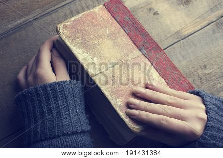 woman opens the book to read on table