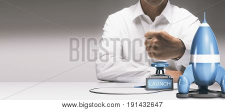Man about to press a push button to launch a spaceship. Advertising concept of launching a new product or service. Composite between a 3D image and a photography background.