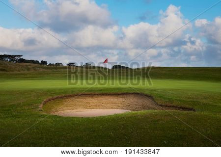 A golf course showing a pristine new bunker, green and flag.