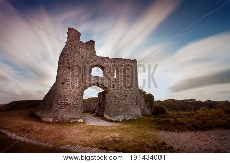 Sweeping clouds over the remains of Pennard castle on the Gower peninsula, overlooking Three Cliffs Bay, Swansea, South Wales, UK