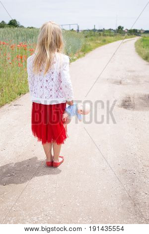 little girl with doll in the street