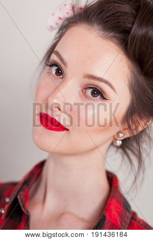 beautiful young woman on white background in old fashion clothes representing pinup and retro style.