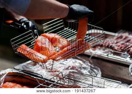 Cook in black gloves cooks red fish barbecue on grill