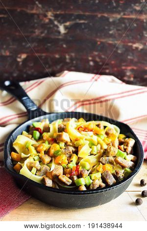 Homemade pappardelle pasta dish with pumpkin, avocado, chili pepper and pork meat in a pan on a wooden table, selective focus