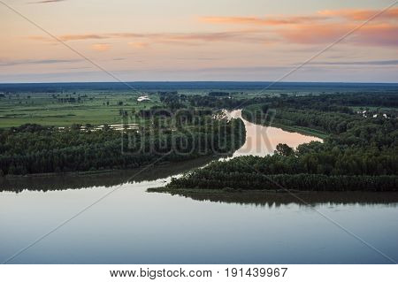 Mirror surface of water at sunset. Altai region. Islands on the river.