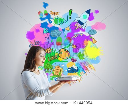 Side view of young woman holding open book on grey background with bright colorful sketch. Innovation concept