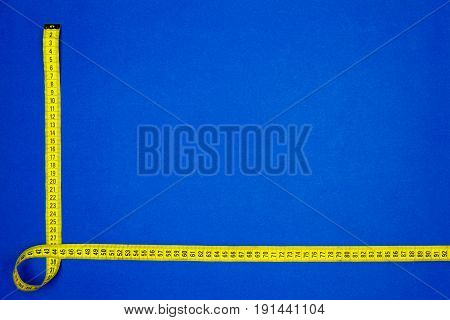 Yellow measuring tape isolated on blue background
