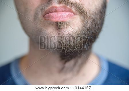 Close up image of lower part of man's face with half shaved beard