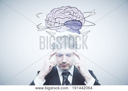 Pensive businessman with abstract brain sketch on light background. Brain storm concept