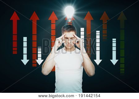 Stressed businessman on dark background with lamp and business chart arrows. Idea concept