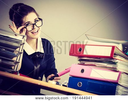 Happy business woman feeling energetic sitting working at desk full off documents in binders.