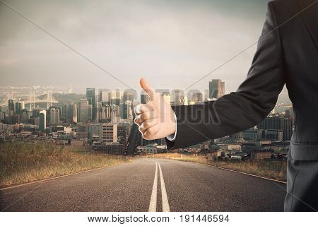 Businessman showing thumbs up on road and city background. Success gesture concept