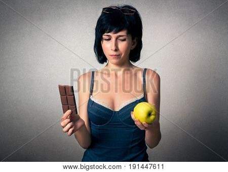 Pretty woman choosing between chocolate and an apple