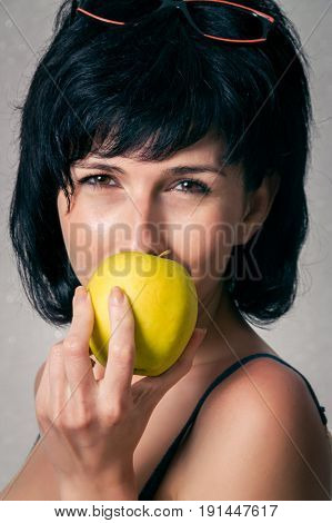 Woman close up with the yellow apple
