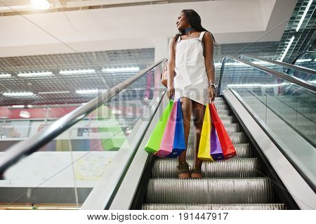Portrait Of A Stunning African American Woman With Multicolored Shopping Bags On Escalator.