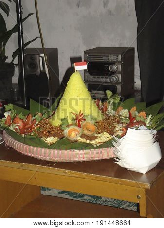 Nasi tumpeng is a yellow cone shaped rice form, people usualy round them to eat together after several rituals.
