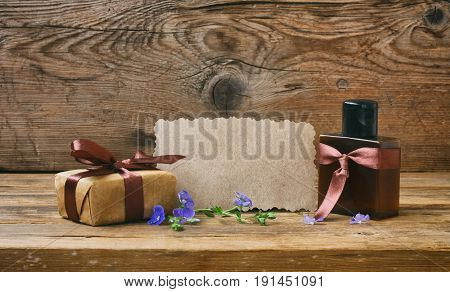Fathers Day card gift box with brown ribbon perfume bottle paper tag on a wooden table
