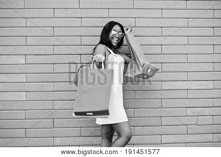 Portrait Of A Fantastic African American Woman Wearing Sunglasses Holds Multicolored Shopping Bags O