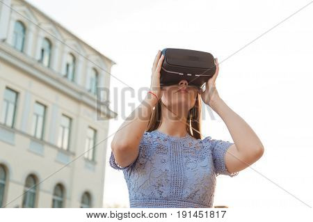 Young brunette is amused by her first encounter with futurist virtual reality glasses.