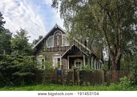 Small beautiful wooden house in the village among the green trees Pskov Region Russia