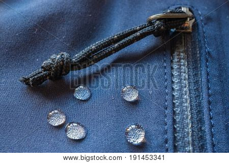 large rain drops dew on dark waterproof weatherproof membrane clothes. closeup macro shot of buckle zipper sealed pocket fastener