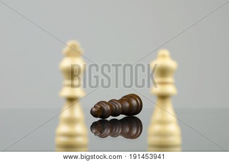 Close-up view of two wooden white chess pieces defeating a black chess king with a reflection in the glass