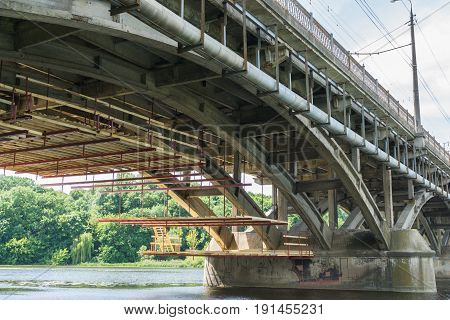 upgrading and repair of the automobile bridge over the river. low angle shot from the ground under the bridge. wooden scaffolding