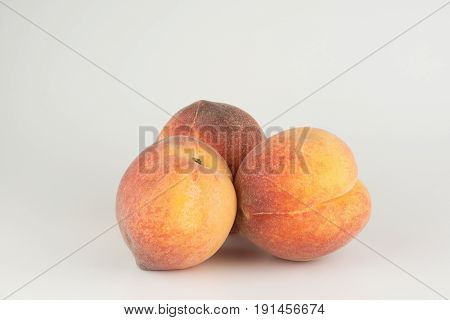 Three large ripe peaches on a white background