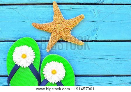 pair of flip-flops on blue wooden background and starfish
