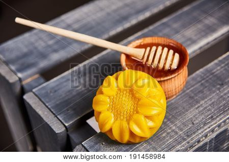 wooden stick and wooden bowl for honey on the wooden crate