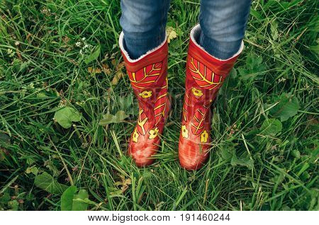 Feet shod in red rubber boots in flower standing on the grass