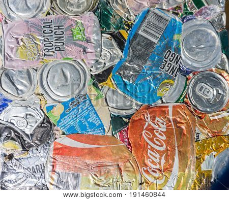 Alofi, Niue, May 29, 2017; Compressed aluminium drink cans with branding showing ready for recycling.