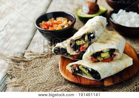Rice black bean avocado tomato burritos on a wood background