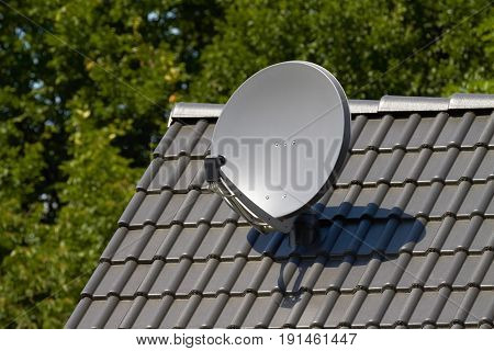 Satellite dish on the roof of a house.