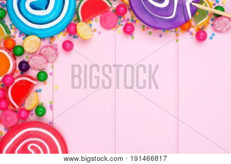Top Corner Border Of Assorted Colorful Candies Against A Pink Wood Background