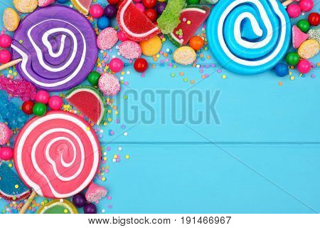 Top Corner Border Of An Assortment Of Colorful Candies Against A Blue Wood Background
