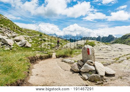 Trail sign in the mountains. Trekker walking in the distance.