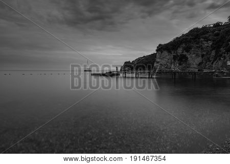Wooden dock at the beach with blurred water at sunset and sail boat in the background in black and white