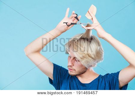 Style and fashion. Young trendy male hairstylist barber with new idea of look changing. Blonde guy with scissors and wooden comb creating hairdo coiffure on blue