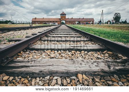 Oswiecim Poland - June 14 2017: Auschwitz-Birkenau concentration camp main gate with railway track on June 14 2017 in Oswiecim Poland.