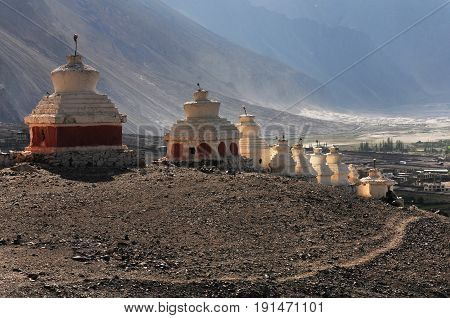 A series of ancient white Buddhist stupas with a red base settled on the of the mountain in the rays of the setting sun Tibet the Himalayas.