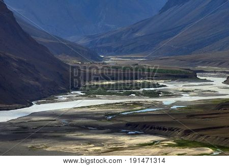The river bed of the high mountains: a water stream flowing among the high banks among the sandbanks small green fields and dark mountain slopes Himalayas.