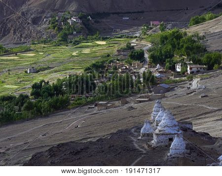 Ancient white Tibetan stupas in a row on a mountainside and an ancient Buddhist monastery over a mountain village Tibet Himalayas.