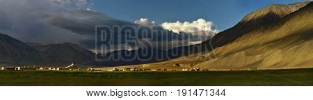 Ancient Buddhist monastery amidst a huge mountain valley at sunset Tibet the Himalayas.
