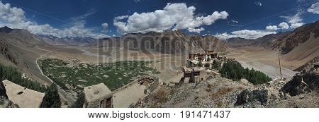 Ancient Buddhist monastery Stongde Gonpa rises on a rock among the huge mountain valley of Zanskar panoramic photograph the Himalayas Northern India on a summer day.