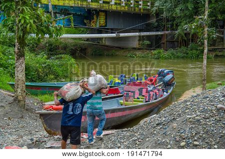 CUYABENO, ECUADOR - NOVEMBER 16, 2016: Unidentified people holding on his shoulders sacks to the boat, inside of Amazon Jungle in Cuyabeno National Park, Ecuador.