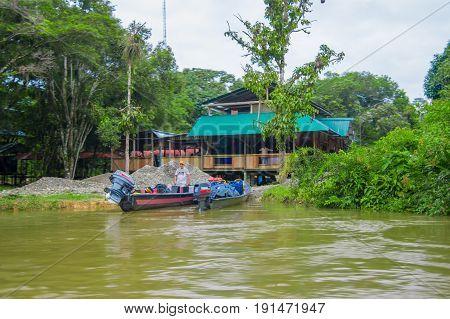 CUYABENO, ECUADOR - NOVEMBER 16, 2016: Unidentified man on a boat in the Cuyabeno river, depth of Amazon Jungle in Cuyabeno National Park, Ecuador.