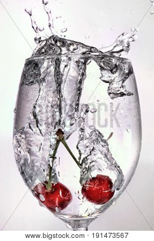 Cherries dropped into a wineglass of water