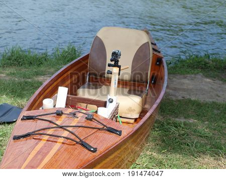 A front to end view of a hybrid kayak made of cedar wood fence post and equipped with a mounted action-type camera for videos.
